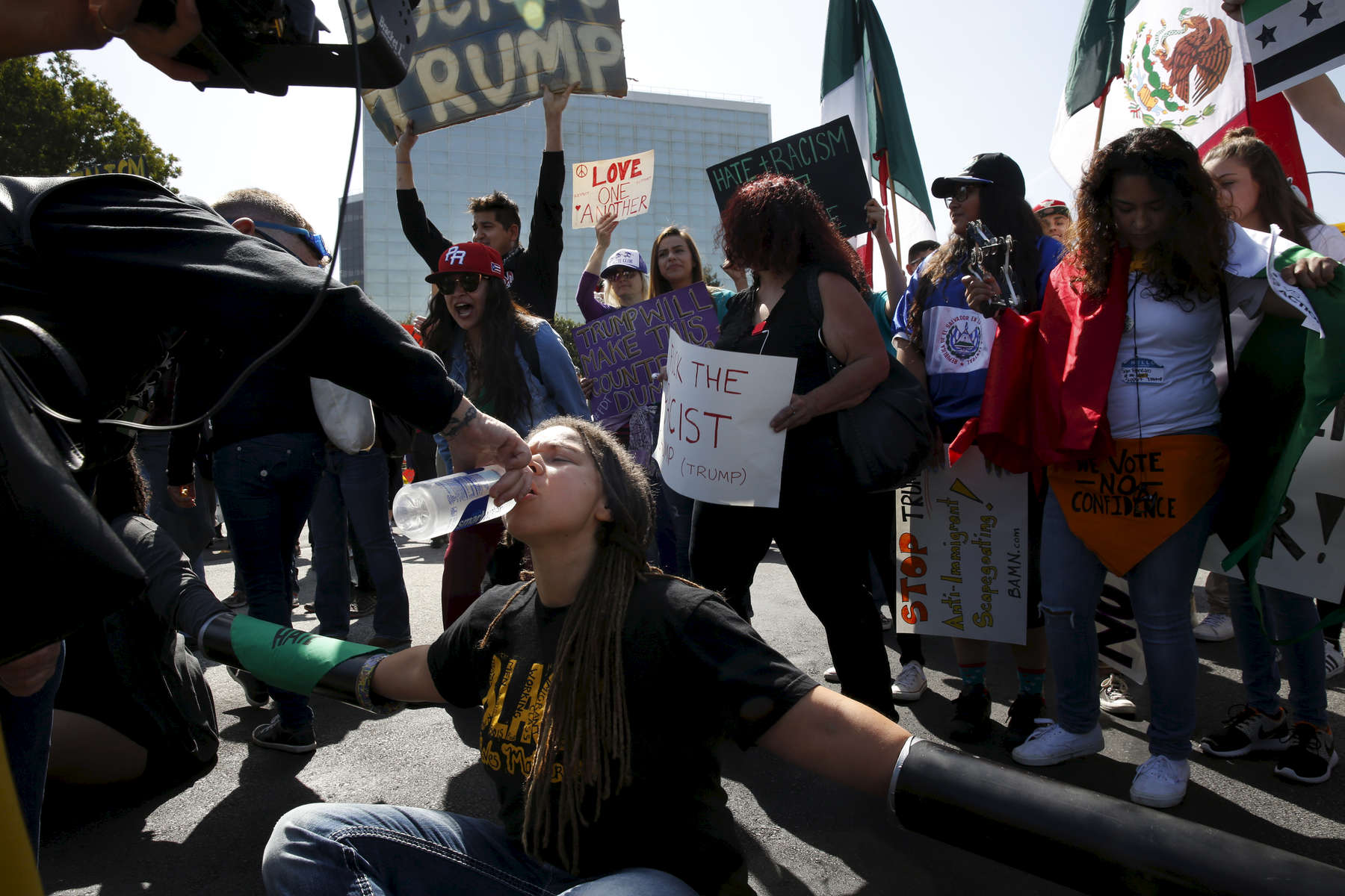 Melissa Crosby gets a drink of water from another protester after chaining herself with other protesters to block off access roads outside of the Hyatt Regency during the first day of the California Republican Party Convention which featured speeches from Presidential candidates Donald Trump and John Kasich among others April 29, 2016 in Burlingame, Calif.