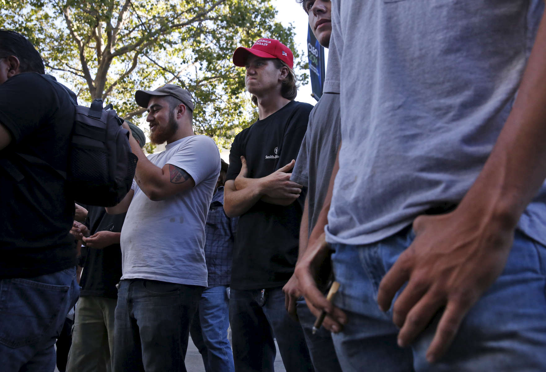Trump supporters including Ian Churchill, 19, center, and Brendan Ortman, 21, left, watch anti-Trump protesters near the convention center before presidential candidate Donald Trump held a campaign rally June 2, 2016 in downtown San Jose, Calif.