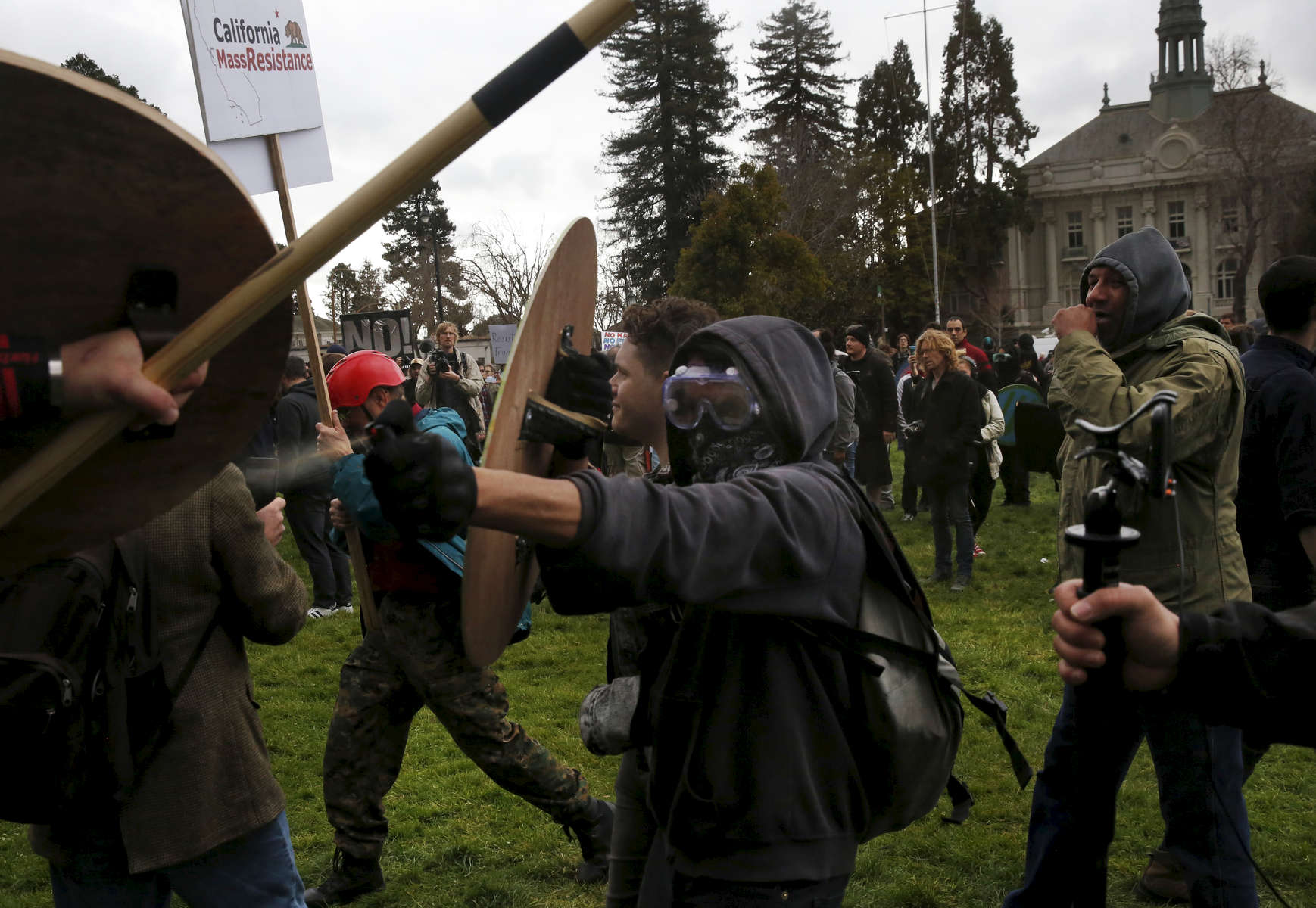 An anti-fascist anarchist sprays pepper spray directly at a Trump supporter after a Trump supporter pepper sprayed the crowd during a pro-President Donald Trump rally and march at the Martin Luther King Jr. Civic Center park March 4, 2017 in Berkeley, Calif.