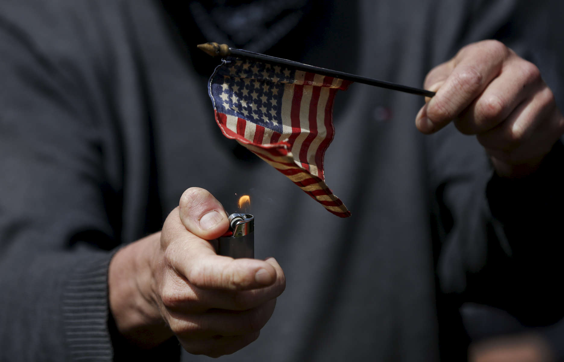 A man attempts to burn a flag while standing with anti-fascist protesters before a rally called {quote}Patriot's Day Free Speech Rally{quote} in Martin Luther King Jr. Civic Center Park April 15, 2017 in Berkeley, Calif.