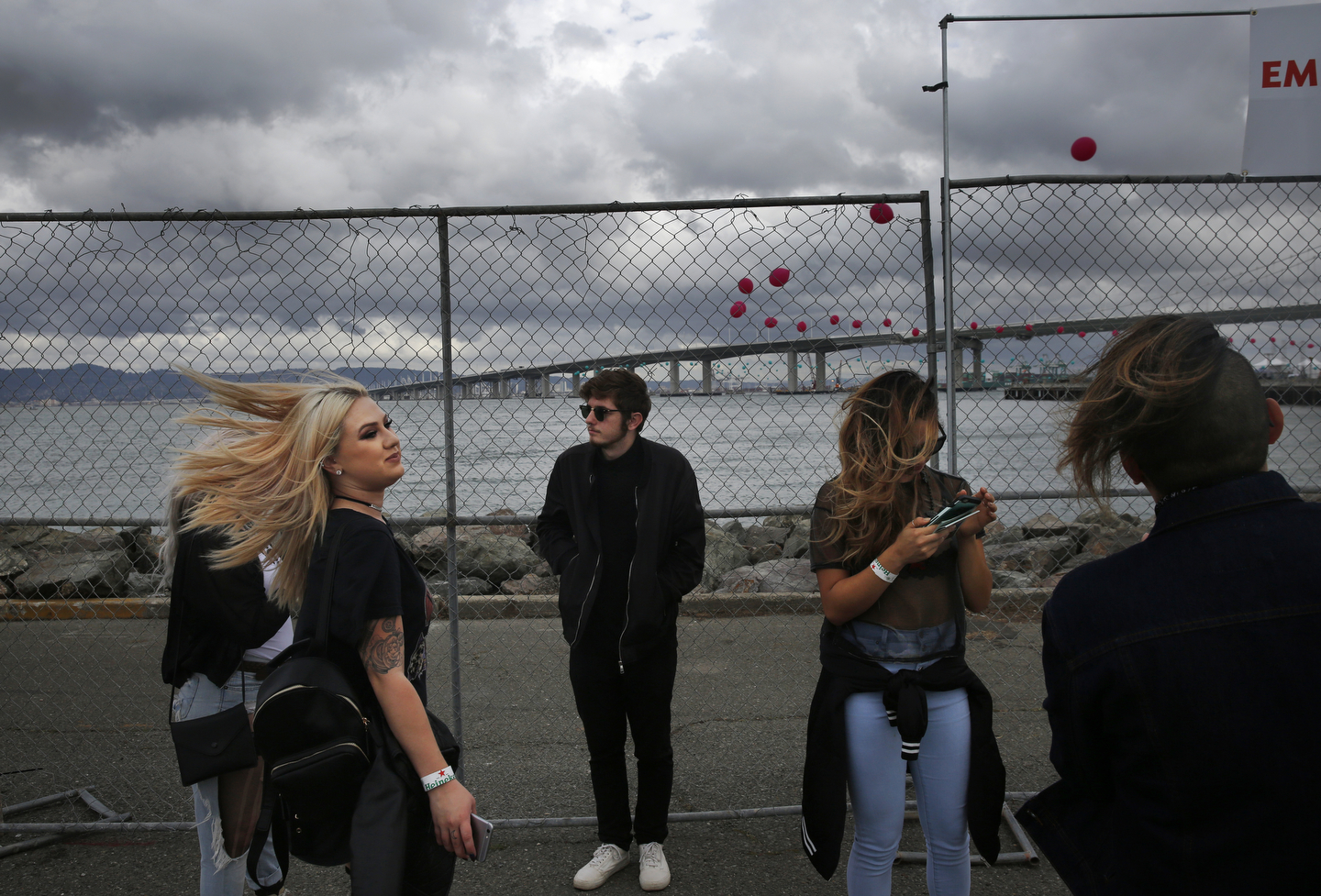 Friends, from left, Angelica Roessert, 21, (not visible) Jennifer Lee, 21, Alex Dernoncourt, 19, Jessica Hanes, 22, and Alan Martinez, 22, hang out and pose for photos with the Bay Bridge in the background as storm clouds approach during first day of the Treasure Island music festival Oct. 15, 2016 in San Francisco, Calif.