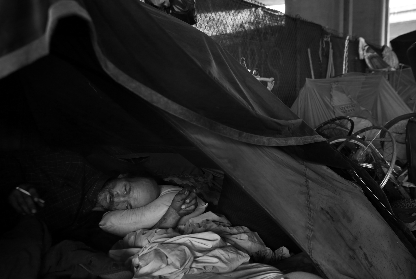 Jeffrey {quote}New York{quote} Hill rests in his tent underneath an overpass on Brush street Aug. 10, 2016 in Oakland, Calif. Hill has been homeless for about six years and has recently seen a big increase in homeless people moving into the area in Oakland.