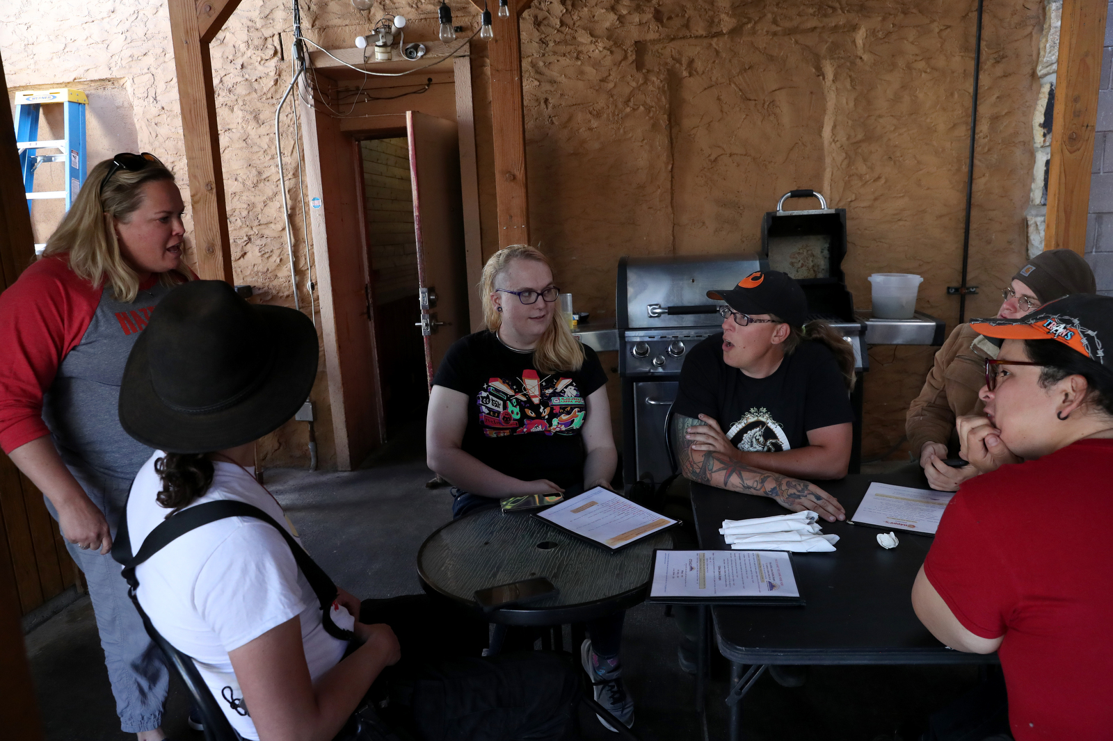 Members of the Tenacious Unicorn Ranch, from left, J Stanley, Kathryn Gibes, Penny Logue, Sky Nelson and Bonnie Nelson greet a woman, who preferred not to give her name, who just moved to the area with a transgender child as they wait for lunch at one of their favorite spots to eat in town, Chappy's Bar and Grill, in Westcliffe, Colorado.