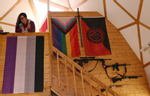 """Bonnie Nelson chats with people as Nelson stands above the asexual flag as it hangs with several other flags representing gender and sexual identity at the Tenacious Unicorn Ranch in Westcliffe, Colorado. Above four mounted rifles, a red-and-black flag can be seen that says, """"Sometimes antisocial, always antifascist,"""" with the three arrows of the Iron Front, a World War II-era German paramilitary anti-Nazi, antifascist organization."""