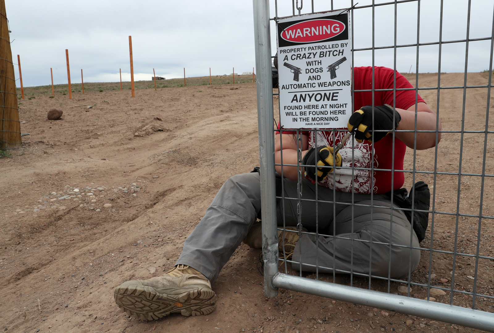 Bonnie Nelson puts up a warning sign on the front gate of the Tenacious Unicorn Ranch. Armed people were previously caught trying to trespass on the property, according to the ranchers.