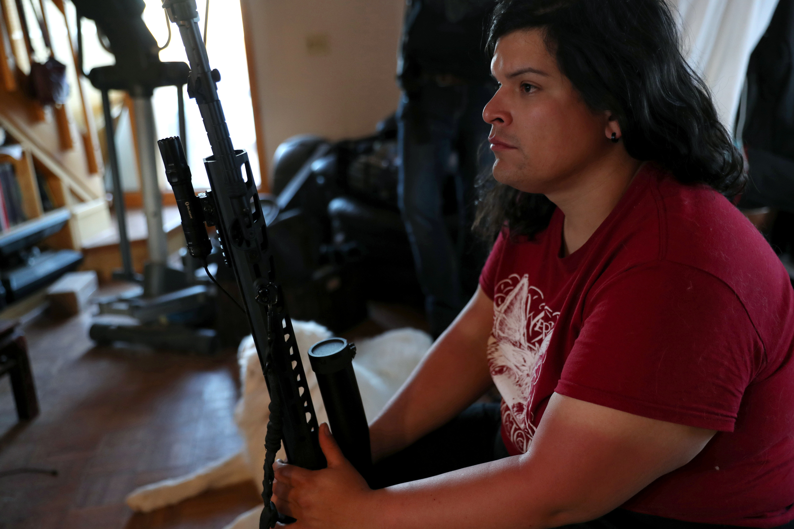 Bonnie Nelson sits with Nelson's rifle, nicknamed Yoko in the living room of the ranch house at the Tenacious Unicorn Ranch. Nelson, who used to be uncomfortable with guns, bought the rifle after witnessing Westcliffe's July 4th protest in 2020, which featured some banners and flags that reminded Nelson and Logue of fascism.