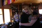 Penny Logue hugs one of her partners, Kathryn Gibes in their home.