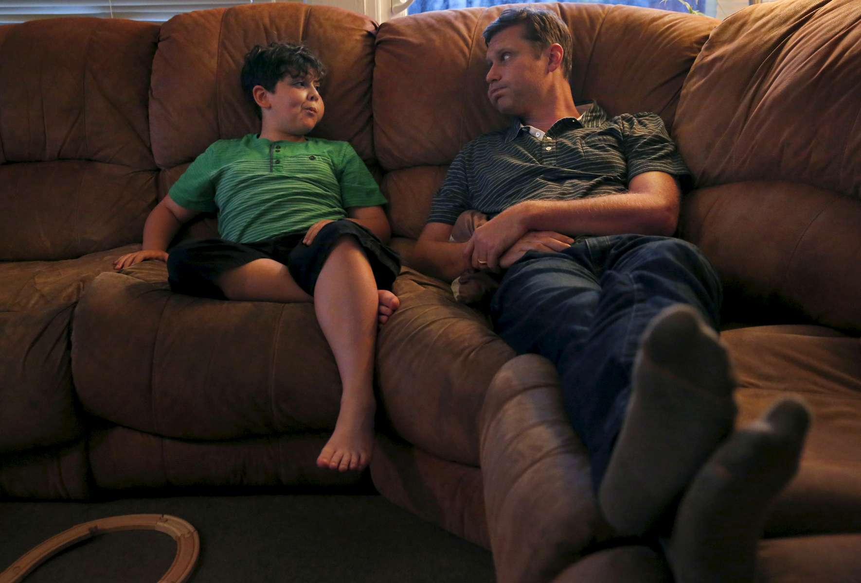 James Kaplan, 8, and his father Ben Kaplan make faces at each other in the living room in the evening Oct. 13, 2016 in Berkeley, Calif. Ben says James used to drop hints about who he was inside before he came out as transgender to his parents. Ben says James even told him he thought there was a boy inside of himself, but Ben didn't get the hint until James came out to a friend and a teacher at school.
