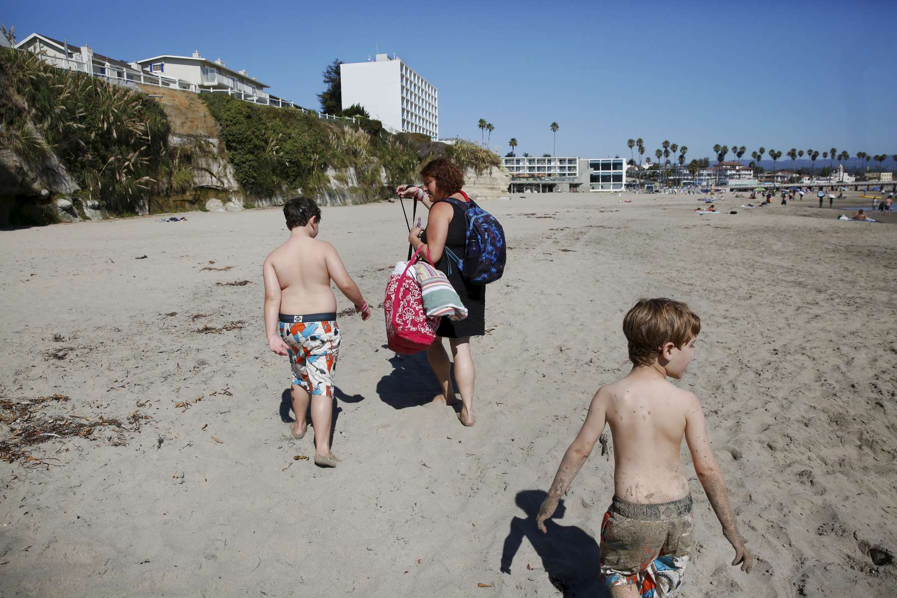 From left, siblings James Kaplan, 8, and Charley Kaplan, 4, walk back to their hotel with their mother Sara Kaplan after a surfing lesson during a family trip Oct. 9, 1016 sponsored by Focus on Cancer in Santa Cruz, Calif. Sara, who survived kidney cancer, was sponsored by the company which works with cancer patients and survivors and their loved ones to provide support and special trips to reduce social isolation. Since the reporting of this story, Charley has been living as a girl. She is wearing dresses, growing her hair out and has taken a more feminine name.
