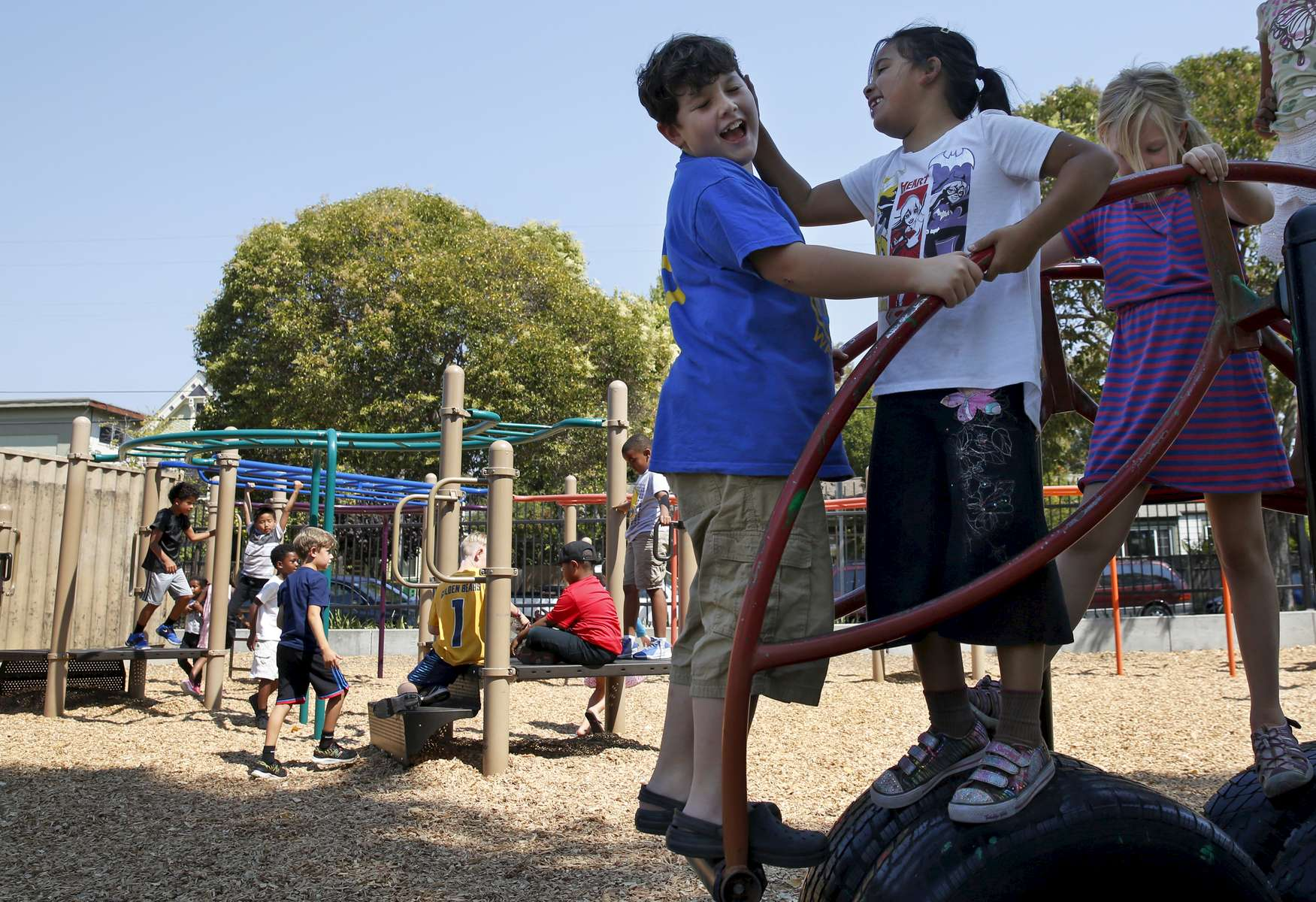 James Kaplan, 8, plays with friends, from left, Rose Herbert, 8, and Serene Kimball, 8 on the playground after school Sept. 7, 2016 in Berkeley, Calif. Rose was the first person James came out to about being a transgender boy.