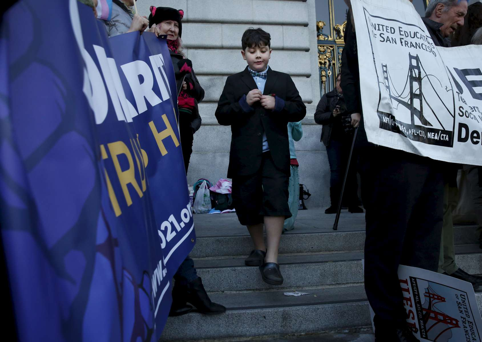 James Kaplan, 9, walks between sign holders after getting a snack on the front steps of City Hall during a Rally to Support Trans Youth after his mother read a letter to the crowd that he wrote Feb. 23, 2017 the day after President Donald Trump removed Obama era bathroom access recommendations in San Francisco, Calif.
