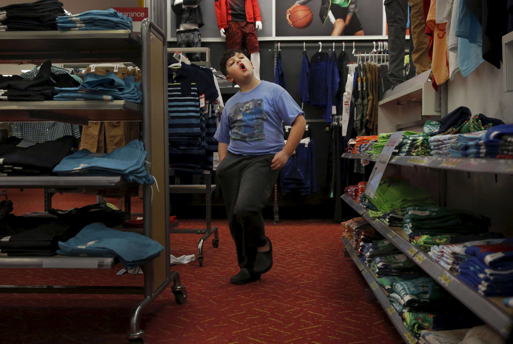 James Kaplan dances through the boy's section at Target Feb. 17, 2017 in Berkeley, Calif. while finding dress clothes with his mother and sibling.