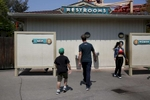 James, 8, and Ben Kaplan walk towards the men's bathroom together while enjoying a family outing to Six Flags amusement park Aug. 20, 2016 in Vallejo, Calif.