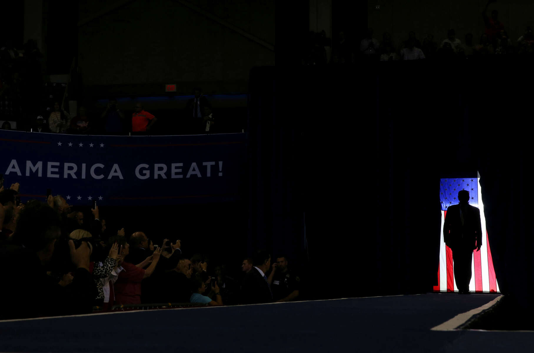 U.S. President Donald Trump is silhouetted against a U.S. flag as he holds a campaign rally in Lake Charles, Louisiana, U.S., October 11, 2019. Throughout the year and his presidency, Trump has continued to hold rallies and often uses them as an outlet to release his frustration and rage with the Democratic Party and the news media.