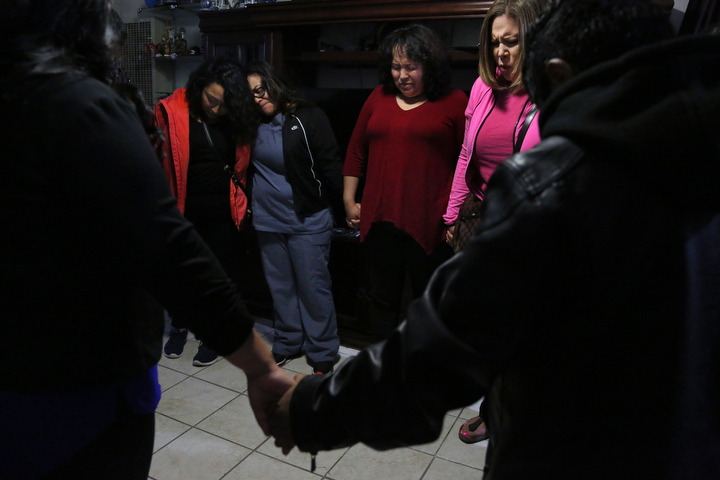 Maria Mendoza-Sanchez, center right, bows her head as her friend Tina Chaney, far right, leads a group prayer in the Sanchez living room with Vianney Sanchez, 23, left, Veronica Perez and other family and friends before the group left to see Maria, Eusebio and Jesus off to Mexico for their ordered self-deportation from SFO August, 16, 2017 in Oakland, Calif.