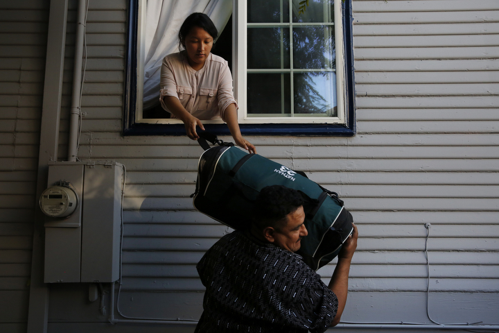 Melin Sanchez, 21, helps her father Eusebio pack the car by handing him luggage through the window August 16, 2017 in their home in Oakland, Calif. The family's application for a stay was denied, forcing Maria, her husband Eusebio and their 12-year-old son Jesus to self-deport, leaving behind their three daughters ages 16, 21, and 23.