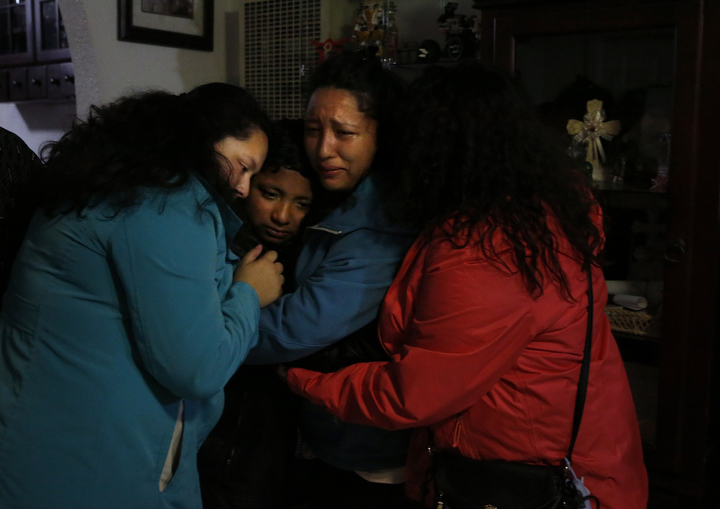 Jesus Sanchez, 12, is held by his three sisters, from left, Elizabeth, 16, Melin, 21, and Vianney after a group prayer in their living room before leaving to see him and their parents off to Mexico from SFO August, 16, 2017 in Oakland, Calif.
