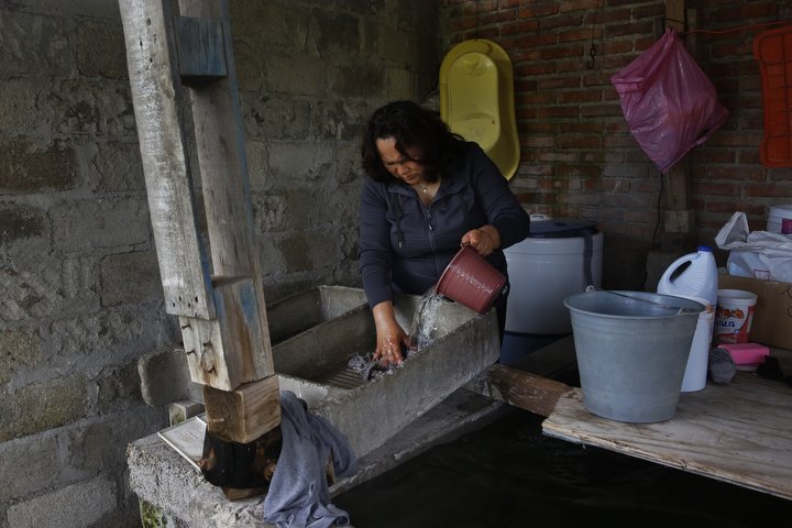 Maria Mendoza-Sanchez rinses a rag in a concrete wash basin behind her mother's home while doing chores around the house Sept. 28, 2017 in Santa Monica, Hidalgo, Mexico.