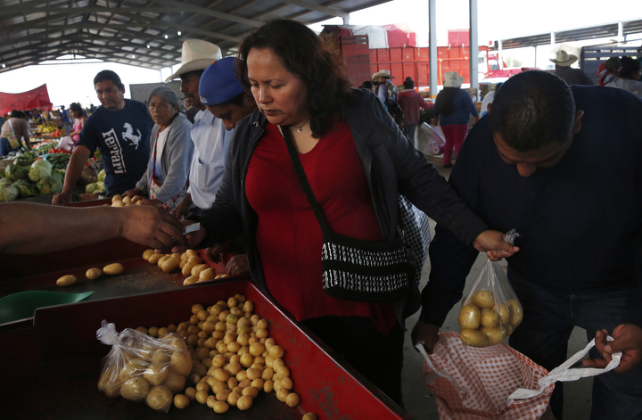 Maria Mendoza-Sanchez purchases vegetables with her husband, Eusebio Sanchez, right, and some of their family at a market near Santa Monica, Hidalgo, Mexico.