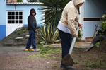 Jesus Sanchez, 12, watches his grandmother Juana Alamilla Olguín, 69, for technique as he helps clear weeds in front of her house as a light rain falls Sept. 30, 2017 in Santa Monica, Hidalgo, Mexico.