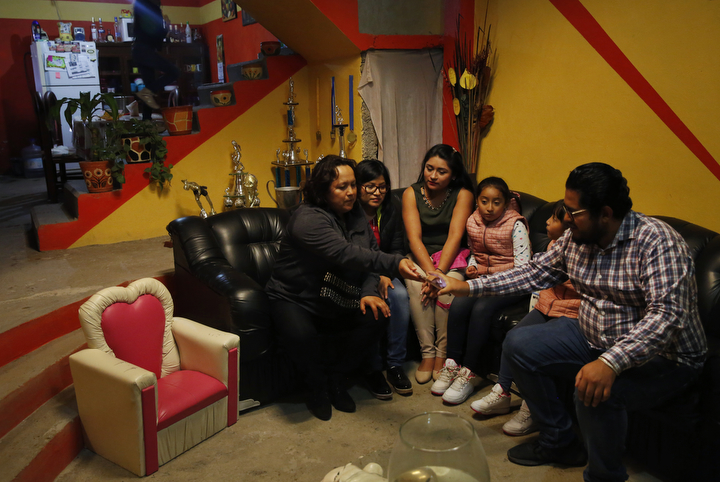 Maria Mendoza-Sanchez passes around photos of a property she owns next door while sitting with family members, from left, Elizabeth Villarreal,     Ariana Sanchez, Ambar Sanchez, 9, Jade Sanchez, 7, and Irvin Sanchez during a visit to check in on her property and take care of related paperwork Sept. 27, 2017 near Mexico City, Mexico.