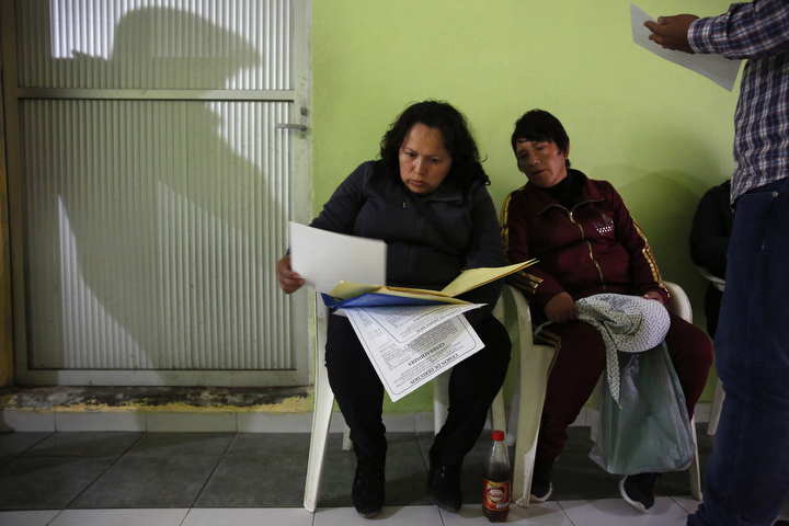 Maria Mendoza-Sanchez sits with family members and most of the neighborhood, including Paulina Vilchis, right, in a government office while trying to sort out paperwork relating to property she and her husband own nearby Sept. 27, 2017 near Mexico City, Mexico.