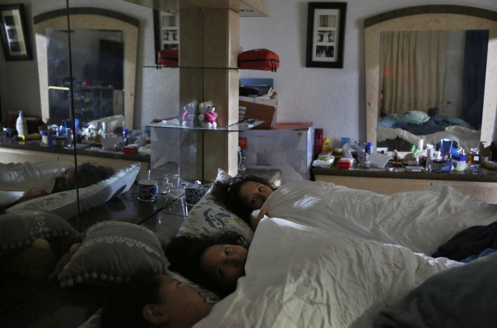 Sisters, from bottom left, Elizabeth, 16, Melin, 21, and Vianney Sanchez, 23, chat before falling asleep for the night in their parent's bedroom Sept. 12, 2017 in Oakland, Calif. The three began sharing their parent's bed once their parents and brother were deported to Mexico. Vianney says she is afraid that if something happens in the front of the house she won't hear it from her room and the three draw comfort from each other's company.
