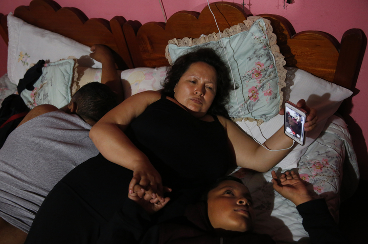 Maria Mendoza-Sanchez and her son Jesus Sanchez, 12, video chat with Jesus' sisters as his father Eusebio Sanchez sleeps next to them before bed in their room which is normally Maria's mother's room in her mother's home Sept. 28, 2017 in Santa Monica, Hidalgo, Mexico. Maria calls her daughters at least once a day every evening to check in on how their days were and to tell them about their lives in Mexico. Maria later sent Jesus back to Oakland because his paperwork did not come through in time at the local school and he would have been held back a year.