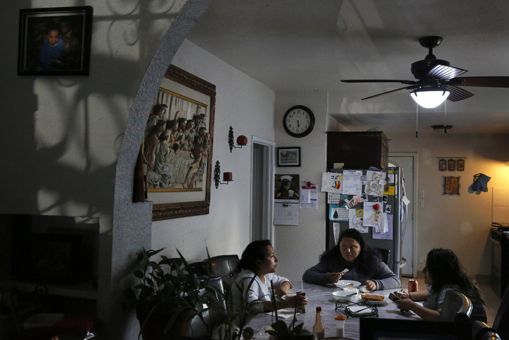 Sanchez sisters from left, Melin, 21, Elizabeth, 16, and Vianney, 23, eat dinner as they wait for their daily video call from their mother in Mexico Sept. 8, 2017 in their family home in Oakland.