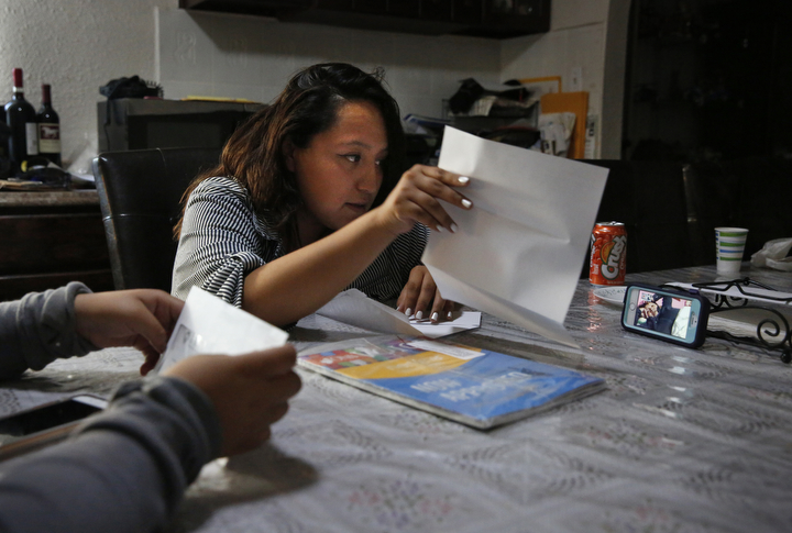 Vianney Sanchez, 23, center, shows her mother Maria Mendoza-Sanchez, lower right, pictured on screen, the mail Sept. 8, 2017 in their family home in Oakland as Vianney and her sisters Elizabeth, 16, left, and Melin, 21 (not pictured) video chat with their mother as she lays in her bed in Mexico. Though she is thousands of miles away, Maria does her best to stay highly involved in her daughter's day-to-day lives. Maria must also continue to pay her mortgage and other bills.