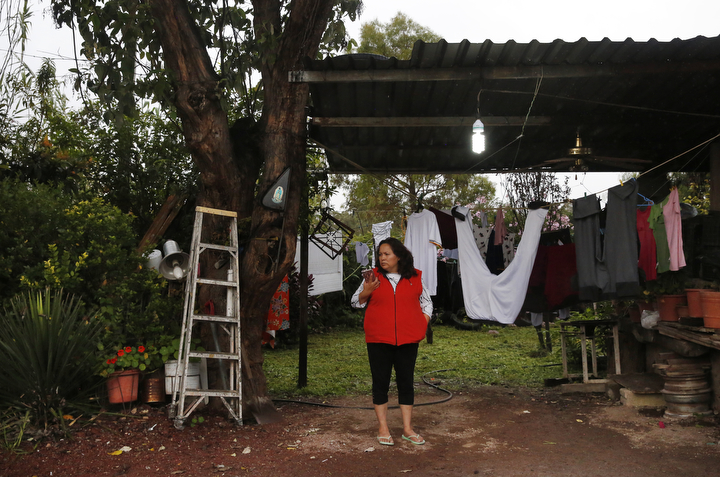Maria Mendoza-Sanchez tries to get service on her cell phone to call her daughters as rain continues to pour down Oct. 1, 2017 in Santa Monica, Hidalgo, Mexico. The weather often interrupts internet and phone service, sometimes for days at a time, cutting her off from her daughters and the rest of the world.