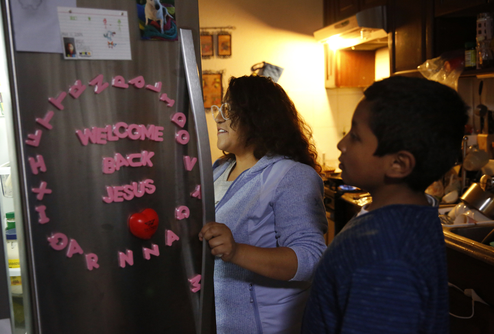 Vianney Sanchez, 23, gets food out of the fridge to make a favorite meal for her little brother Jesus Sanchez, 12, after getting home from the airport where he arrived from Mexico Oct. 14, 2017 in Oakland, Calif. Their mother Maria Mendoza-Sanchez made the decision to send him back to the US after it was discovered that his paperwork hadn't gone through quickly enough for school and he would have to repeat the entire grade over again.