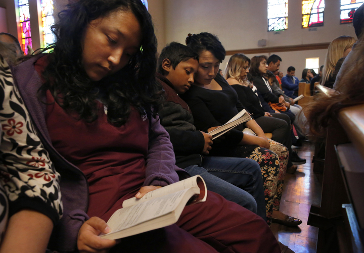 From left, siblings Elizabeth, 16, Melin, 21, Jesus, 12, and Vianney Sanchez, 23, follow the service at their local Catholic church Nov. 5, 2017 in Oakland, Calif. When their parents left Vianney promised their mother that they would attend church services every Sunday and they have, finding a supportive community there. Their mother Maria Mendoza-Sanchez made the decision to send Jesus back to the US after it was discovered that his paperwork hadn't gone through quickly enough for school and he would have to repeat the entire grade over again.