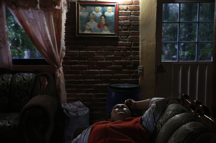 Maria Mendoza-Sanchez lays on a chair, staring at the ceiling of her mother's home as rain falls unrelenting outside, keeping the internet and phone service from working, cutting her off from communication with her daughters Oct. 1, 2017 in Santa Monica, Hidalgo, Mexico. The phone service is very unreliable in the small town Maria now lives in and weather even as benign as high winds can take out the home's internet connection, cutting them off from the outside world. Many days Maria says she simply stares out the window, thinking of her children, her heart aching, wishing she was with them.