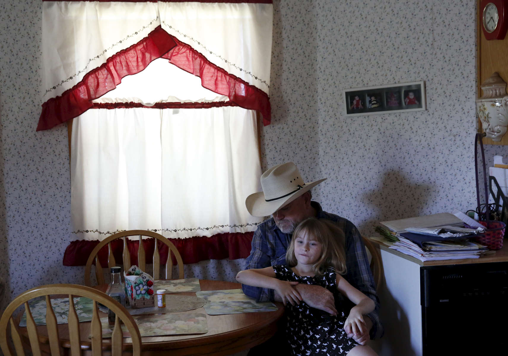 "Dennis Baker, 53, hangs out with his granddaughter Kaylie Baker, 6, before a delayed Father's Day dinner for him June 23, 2015 at his home, situated on his farmland in Tracy, Calif. Baker, who farms 40 acres of hay, became concerned for his crop after a hearing at the San Joaquin County Superior court between the State Water Board and his water district (the Banta-Carbona Irrigation District) was held to decide whether it is legal for the state to stop water diversions to senior water rights holders like him. If the water stopped flowing to his land, he was worried about losing his crop, or more importantly, losing his ""permanent pasture"" which has been reseeding itself for 50 years."