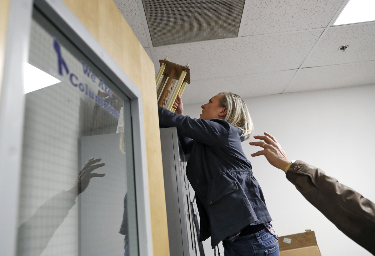 Columbine high school mass shooting survivors Heather Martin, left, and retired Columbine principal Frank DeAngelis check to see if there are still objects left in the room from 20 years ago, where Martin barricaded herself with dozens of other students during the shooting as she, DeAngelis and a handful of survivors tour the school March 17, 2018 in Colorado, US.