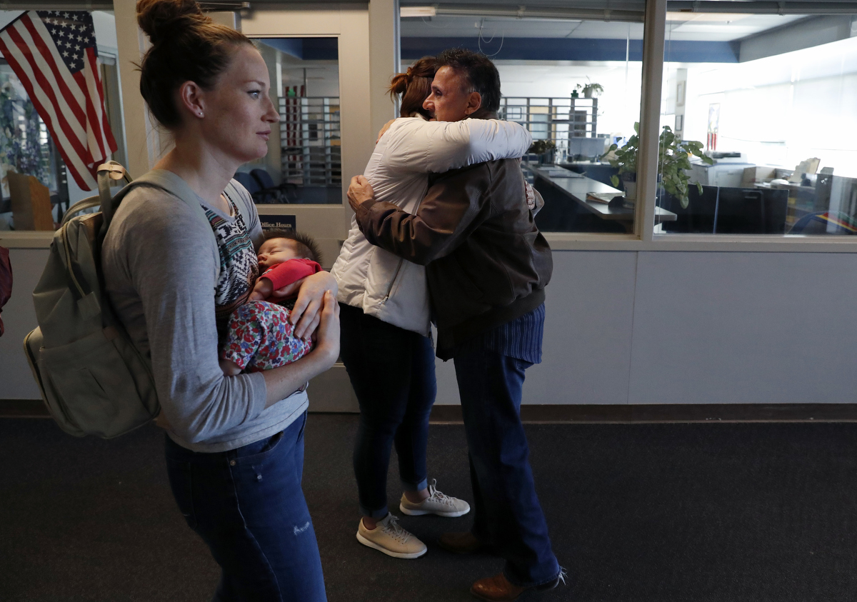 Columbine high school alumni Rachel Burr, center, and Tami Diaz (holding Alayna, 6 wks) say good bye to retired principal Frank DeAngelis after a group of former students and survivors took a private tour of the school March 17, 2018 in Littleton, Colorado, US.