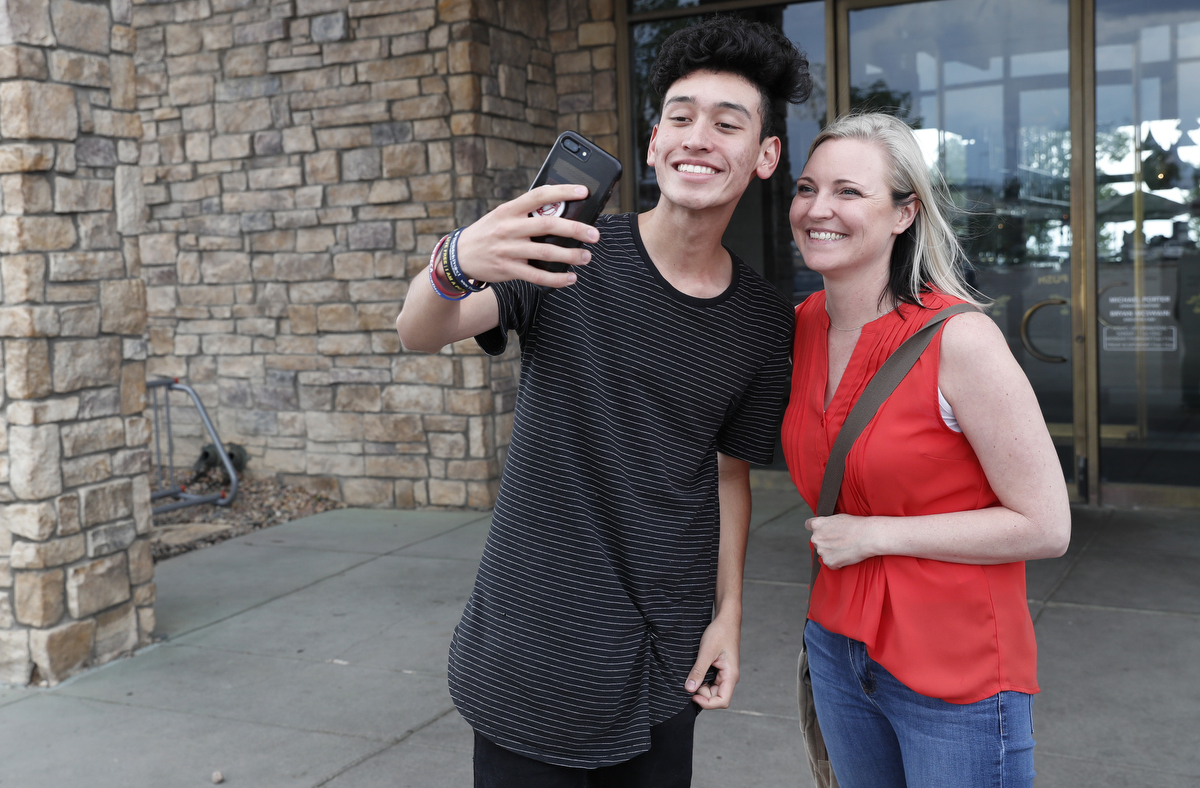 Mass shooting survivors Carlitos Rodriguez, 17, of Marjory Stoneman Douglas poses for a selfie with Heather Martin of Columbine July 24, 2018 outside of a restaurant after they had lunch in Lone Tree, Colorado, US.