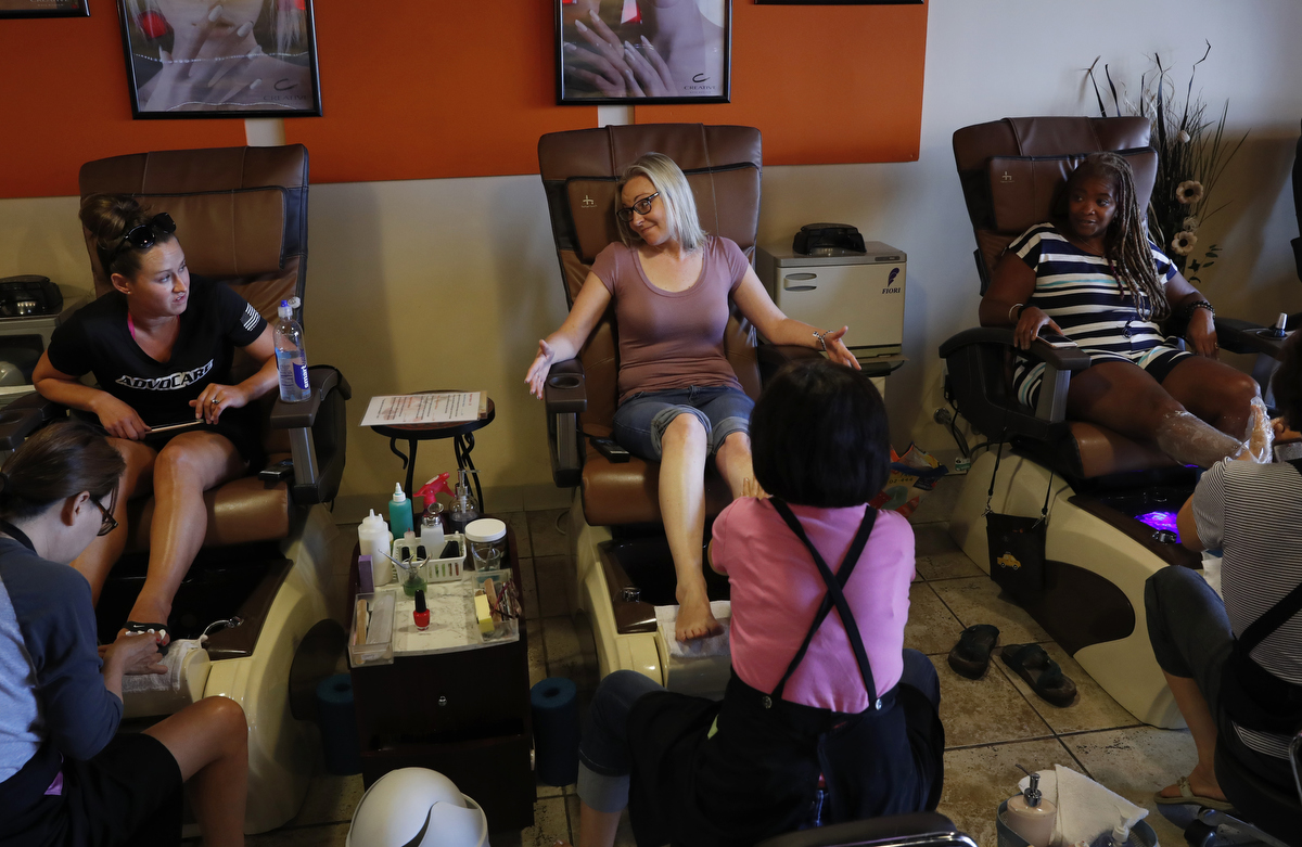 Mass shooting survivors and The Rebels Project leadership team members, from left, Amy Over, of Columbine, Heather Martin, of Columbine and Sherrie Lawson of DC Navy Yard talk about their upcoming annual survivor's gathering while they get pedicures to try to relax July 25, 2018 in Parker, Colorado, US.