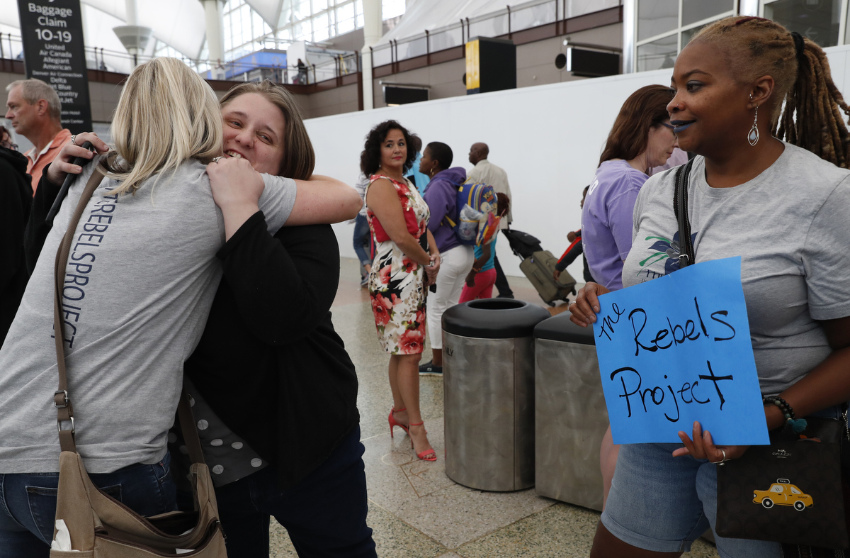 Heather Martin, of Columbine, left, hugs fellow mass shooting survivor Amanda Blomberg of Ft. Lauderdale Airport as Sherrie Lawson of DC Navy Yard looks on while Lawson and Martin pick people up for their annual survivor's gathering from Denver International Airport July 27, 2018, in Denver, Colorado, US.