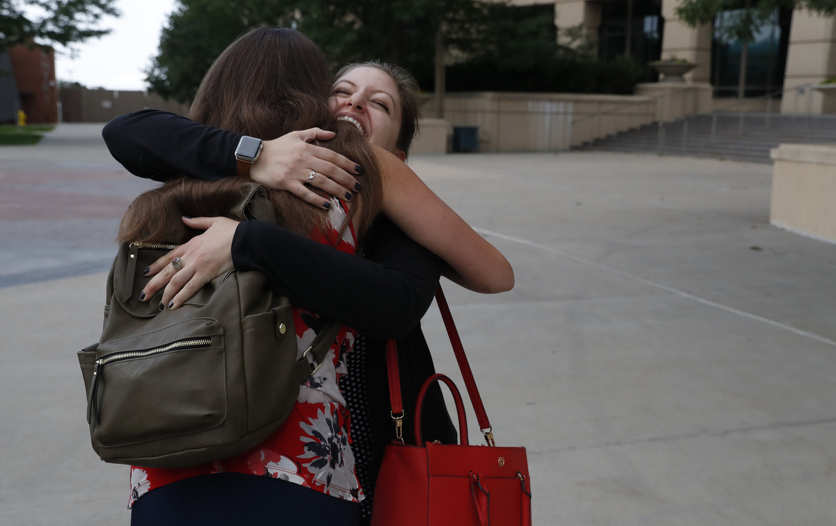 Fellow mass shooting survivors Becca La Creta, right, and Kristina Anderson, both of Virginia Tech, greet each other on their way into a private event for friends and family of Aurora Theater shooting survivors before the grand opening of the theater shooting's memorial July 27, 2018, in Aurora, Colorado, US.