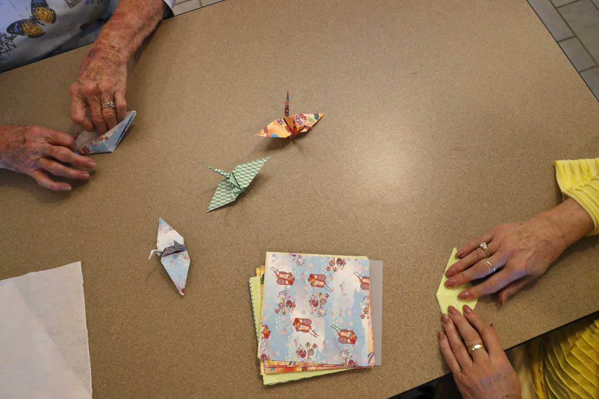 Francie DeLeon, left, and Saundra Foe fold {quote}Peace in our Lifetime{quote} peace cranes during a private friends and family gathering before the grand opening of the Aurora Theater shooting memorial July 27, 2018 in Aurora, Colorado.