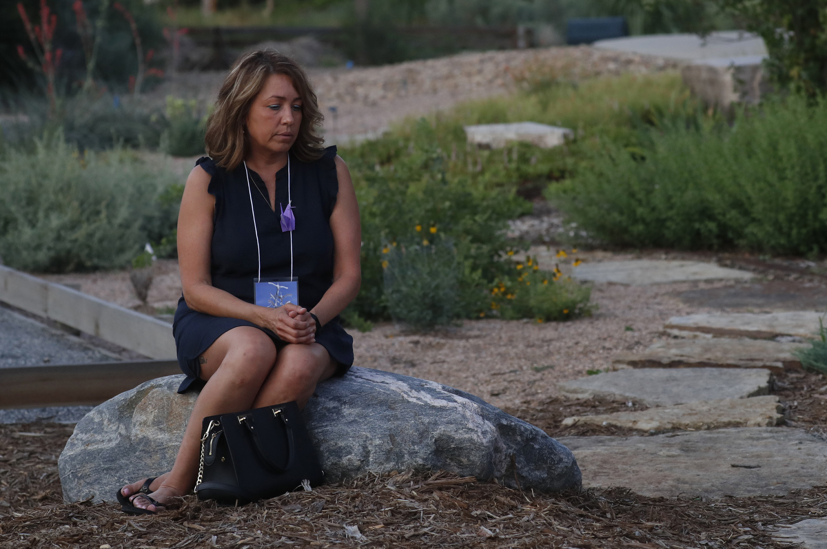 Hedi Bogda, a survivor of the Cedarville Rancheria Tribal Office mass shooting has a quiet moment alone during the grand opening of the Aurora Theater shooting memorial July 27, 2018 in Aurora, Colorado, US.