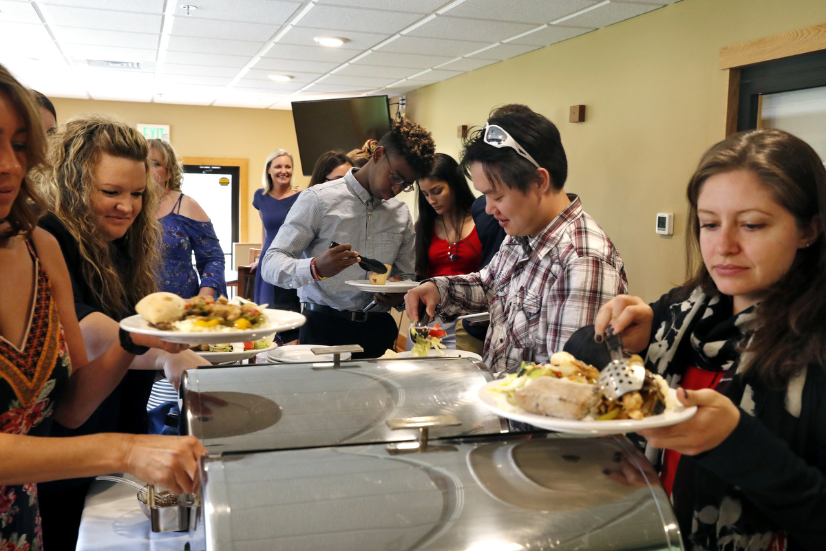 Mass shooting survivors, from left, Hedi Bogda of Cedarville Rancheria, Missy Mendo of Columbine, Heather Martin of Columbine, Chad Williams, 18, of Stoneman Douglas, Ashley Baez, 16, of Stoneman Douglas, Harold Ng of Northern Illinois University and Becca La Creta of Virginia Tech serve themselves food for the luncheon during the annual survivor's gathering with The Rebels Project July 28, 2018 in Englewood, Colorado, US.