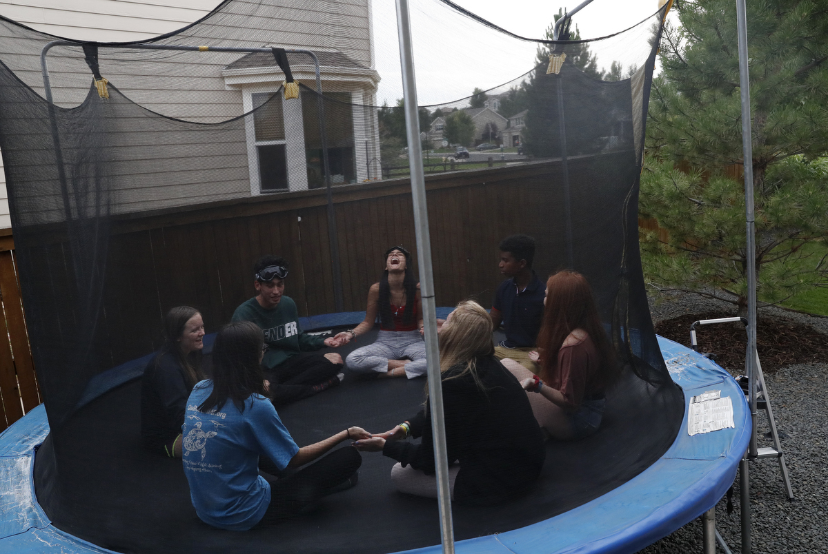 Students and survivors from Stoneman Douglas from top left, Carlitos Rodriguez, 17, Ashley Baez, 16, and Darian Williams, 16, play a game with another Douglas survivor and current Columbine high school students during the family dinner portion of the annual survivor's gathering with The Rebels Project July 28, 2018 in Parker, Colorado, US.