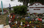 Chad Williams, 19, survivor and former student of Marjory Stoneman Douglas high school, stands alone at a memorial garden created by the girlfriend of Joaquin Oliver, who was was killed in the shooting and was also one of Williams' best friends, March 16, 2019 outside of Marjory Stoneman Douglas high school in Parkland, Florida, US.