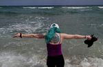 Kaylan Bailey, 20, a survivor of the Aurora Theater shooting, takes in the ocean as she visits the beach with Heather Martin of Columbine and Sherrie Lawson of Washington Navy Yard April 2, 2019 near Ft. Lauderdale, Florida, US. On her back, a tattoo memorializing the event can be seen. The Rebels Project members were invited to Florida to participate in a Parkland MSD Community Peer Support Event.