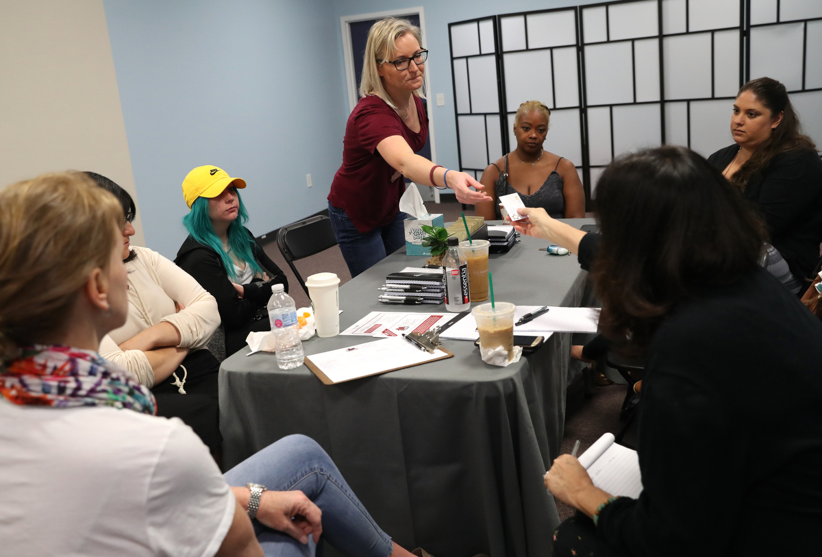 Heather Martin, center, a Columbine survivor, hands her The Rebels Project business card to Julie Gordon, Program Director at Eagles' Haven, a wellness center for the Marjory Stoneman Douglas community during a meeting with The Rebels Project members and two other mass trauma survivors at their new headquarters April 3, 2019 in Coral Springs, Florida, US. The center opened six weeks early after the recent apparent suicides by two Stoneman Douglas students.