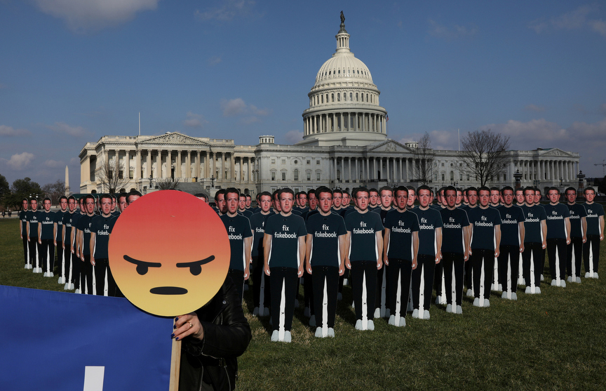 Chelsea Hornick-Becker of Avaaz.org holds a protest sign in front of dozens of cardboard cut-outs of Facebook CEO Mark Zuckerberg outside of the U.S. Capitol Building in Washington, U.S., April 10, 2018. REUTERS/Leah Millis     TPX IMAGES OF THE DAY