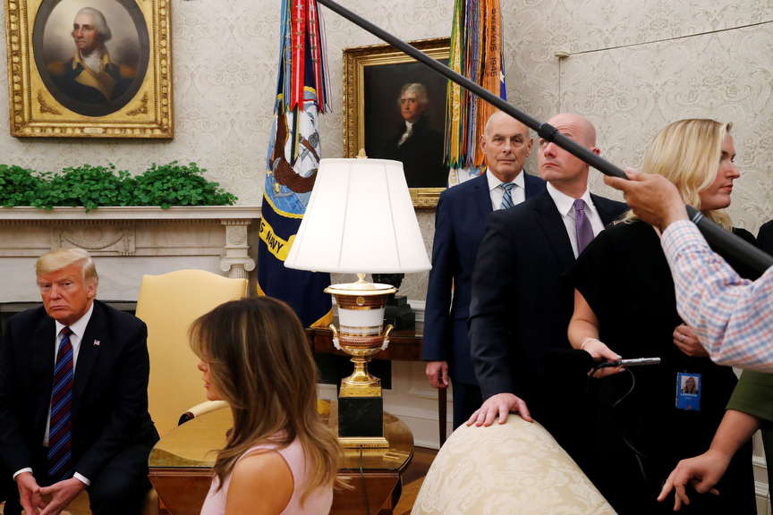 U.S. President Donald Trump ignores questions from reporters about Senator John McCain as news media are escorted from the room at the end of a photo opportunity with Kenya's President Kenyatta as first lady Melania Trump and White House Chief of Staff John Kelly look on in the Oval Office at the White House in Washington, U.S.